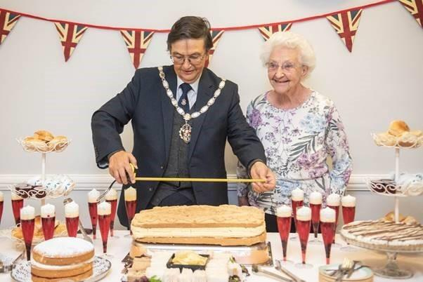 Waltham Abbey Town Mayor Antony Watts and Ashbrook Care Home resident Ruth Hope measure the massive custard cream