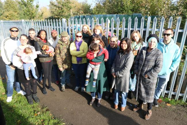 CRDC20191106A..A tall metal security fence has gone up at the Love Lane Community Gardens, South Norwood. Local residents are very upset. Group portrait of concerned local residents and Sarah Jones in front of the fence at the gardens...PLEASE CREDIT..Pho
