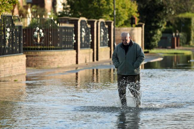 A man walks through floodwater in Fishlake near Doncaster