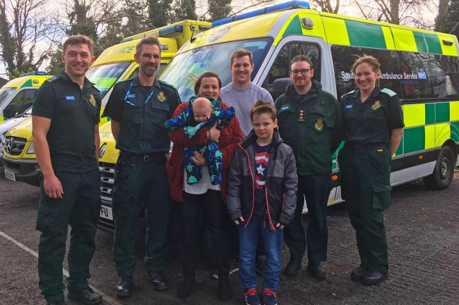 Jayne Rowland and Joshua Mogg with their newborn son Harry, and eight-year-old son Benjamin, alongside members of the ambulance service