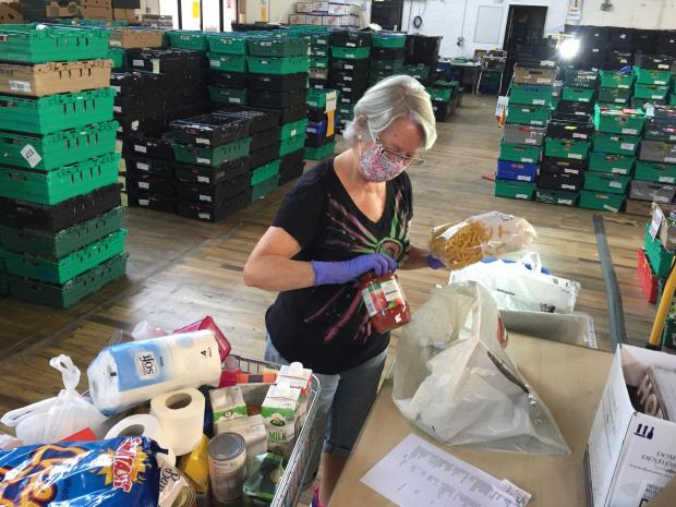 This Is Local London: Volunteer Helen Davis of Bromley packs a kit with seven days worth of meals. Picture: Lachlan Leeming