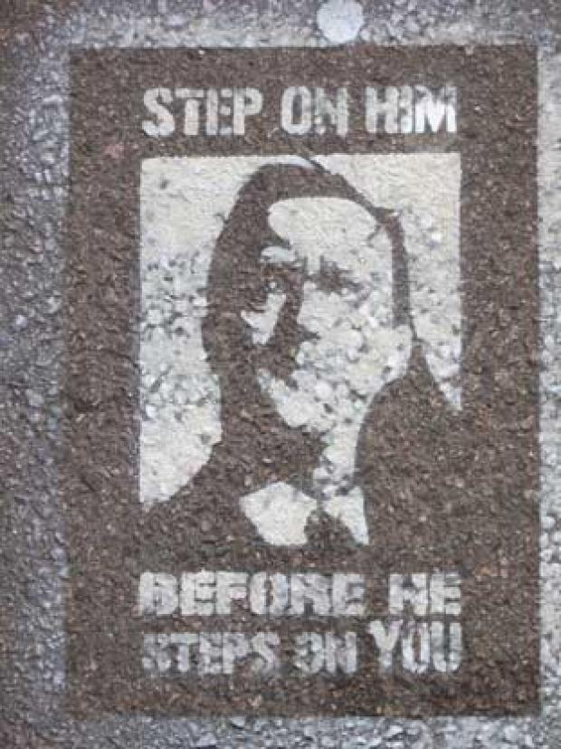 The stencil lies on a pavement approaching Hither Green station.