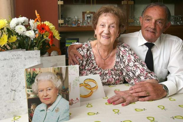 Charlie and Win Tate celebrating their 60th wedding anniversary with a card from the Queen