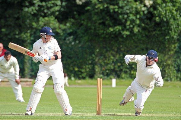 Nervous: Teddington batsman Chris Paget looks on nervously as Eastcote keeper Adam Rossington juggles an attempted catch during Saturday's Middlesex County League Premier Division clash in windy conditions at Bushy Park.