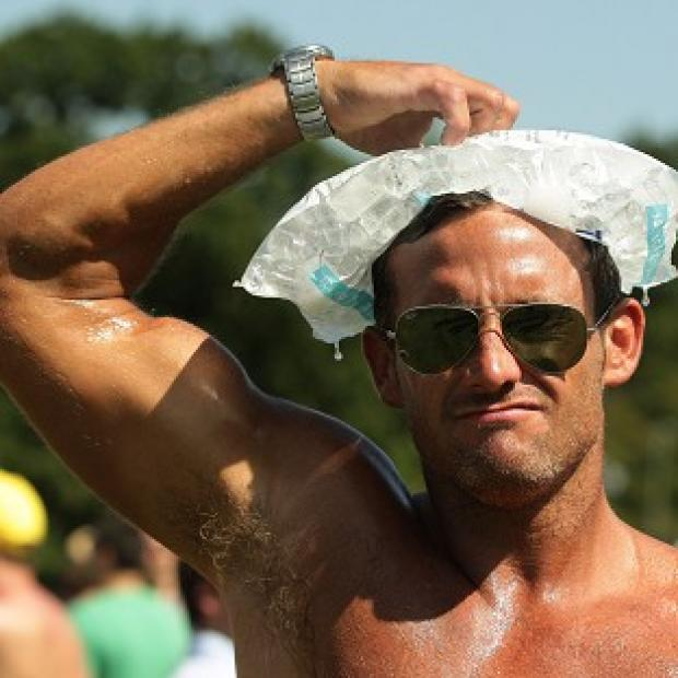 A man cools down with an ice-pack on his head at the V Festival in Hylands Park, Chelmsford