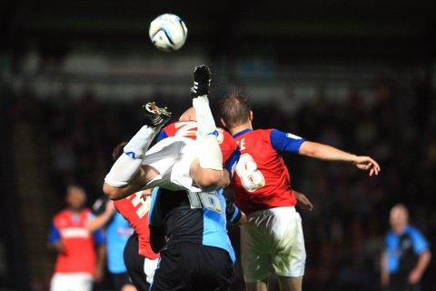 Gillingham's Adam Barrett beats Richard Logan to the ball