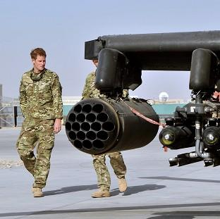 Prince Harry looks over an Apache helicopter at Camp Bastion in Afghanistan