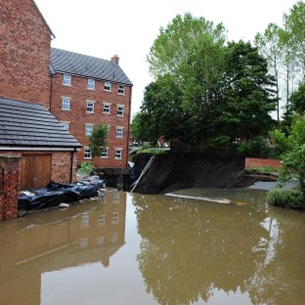 Water cascades past a block of townhouses in Newburn, Newcastle, after floods left them in a state of collapse