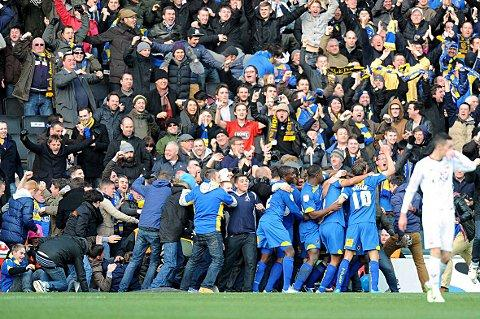 Dons hysteria: AFC Wimbledon players and fans alike celebrate the moment Jack Midson's header brought the scores all level at Stadium MK on an afternoon of high emotion and cruel heartbreak                               				Picture: Press Association