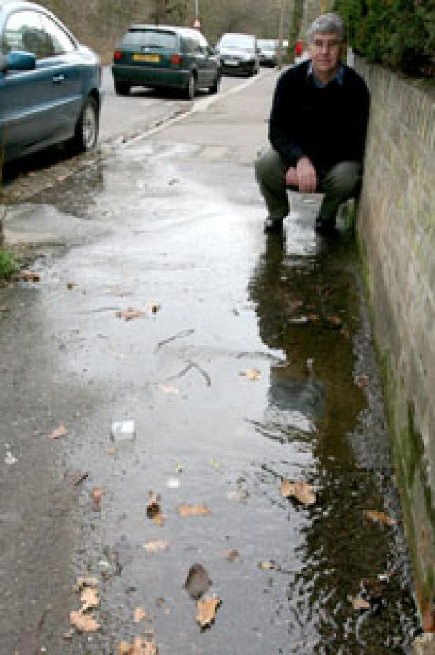 Robert Wilkinson shows where water has been running across the pavement