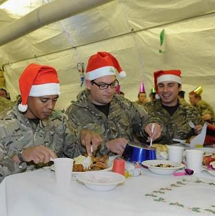 From left, L/Cpl Carlos Da Costa from Jamaica, Cpl Al Butterfill from Doncaster and SAC Curtis Shield from Blackpool enjoy Christmas dinner in Helmand Province
