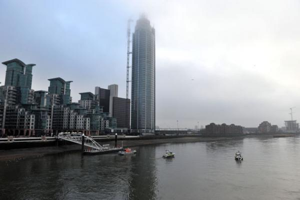Police boats patrol the River Thames in front of the damaged crane on top of St Georges Tower, close to the scene where a helicopter crashed in central London.