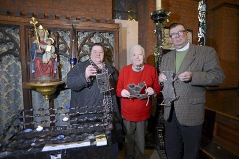 Parish Cllr Heather Stone, longstanding parishoner Pauline Sylvester and Priest Martin Hislop with pieces of broken glass, standing in front of one of the damaged stain glass windows.
