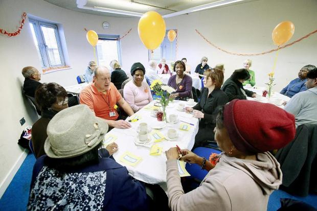Age UK Enfield chief executive Tony Seagroatt with pensioners enjoying the coffee morning