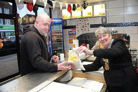 Dartford Mayor Councillor Ann Allen serves Gill's Fish Bar customer Colin Short with some chips.