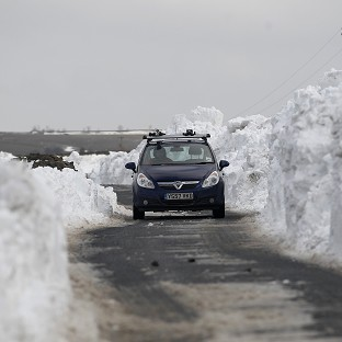 A car makes its way through a wall of snow piled up along a road in the Briercliffe area of Burnley