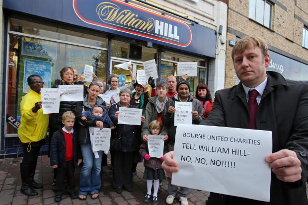 Councillor Clyde Loakes with residents outside a William Hill store