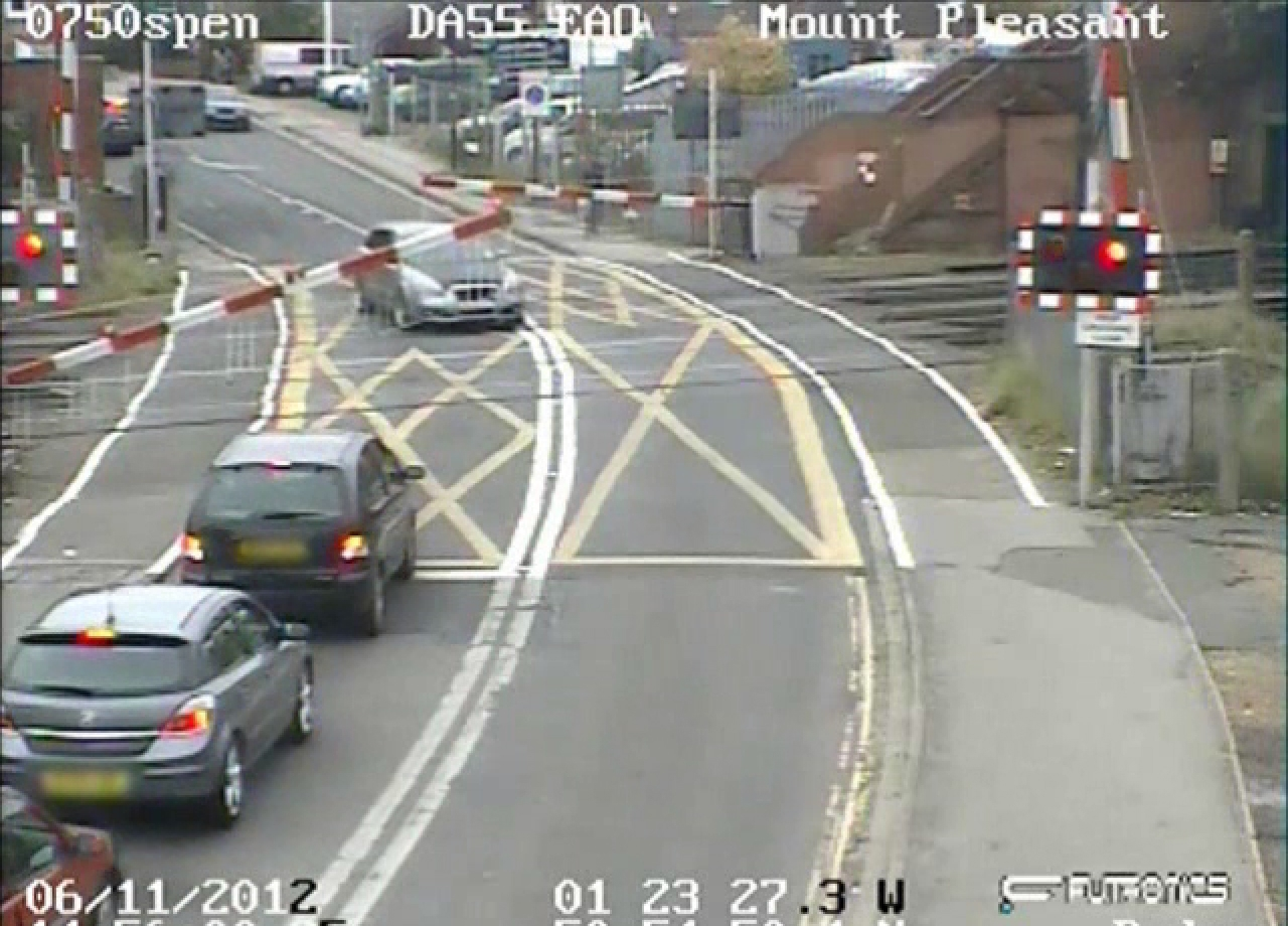 Driver speeds through level crossing as barriers come down - VIDEO