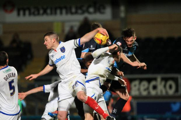 Portsmouth's Ben Chorley appears to handle the ball in a goalmouth scramble after Matt McClure's header