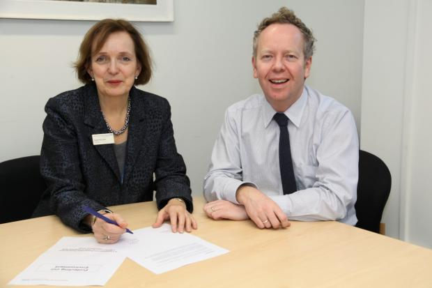 Pledges: Aileen McLeish, chairman of Ashford and St Peter's Hospitals Trust, and Andrew Liles, chief executive, signing the sustainability commitment