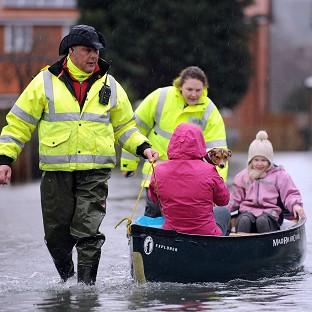 This Is Local London: Volunteers help residents brave the flood water in Purley on Thames.