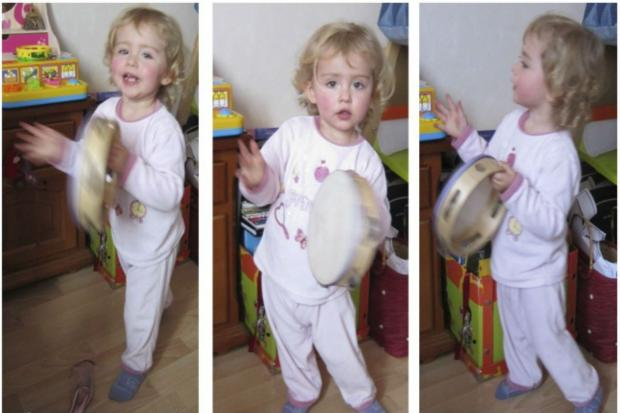Lili playing with a tambourine.