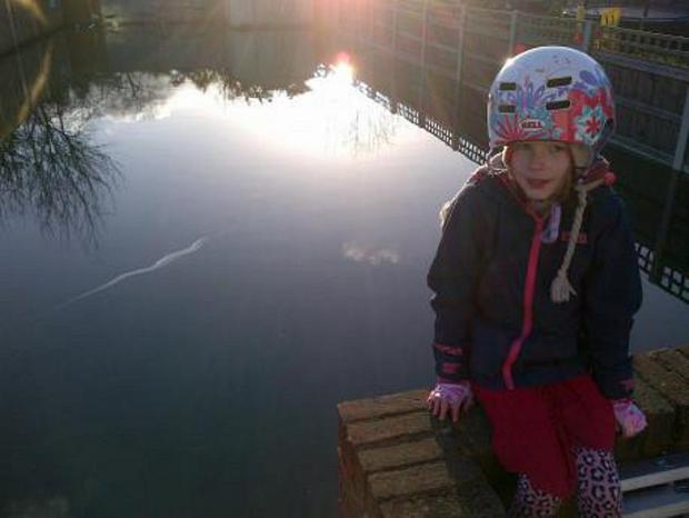 This Is Local London: Farrah Hawkes, aged 9, sitting in her flooded garden in Courtfield Rise