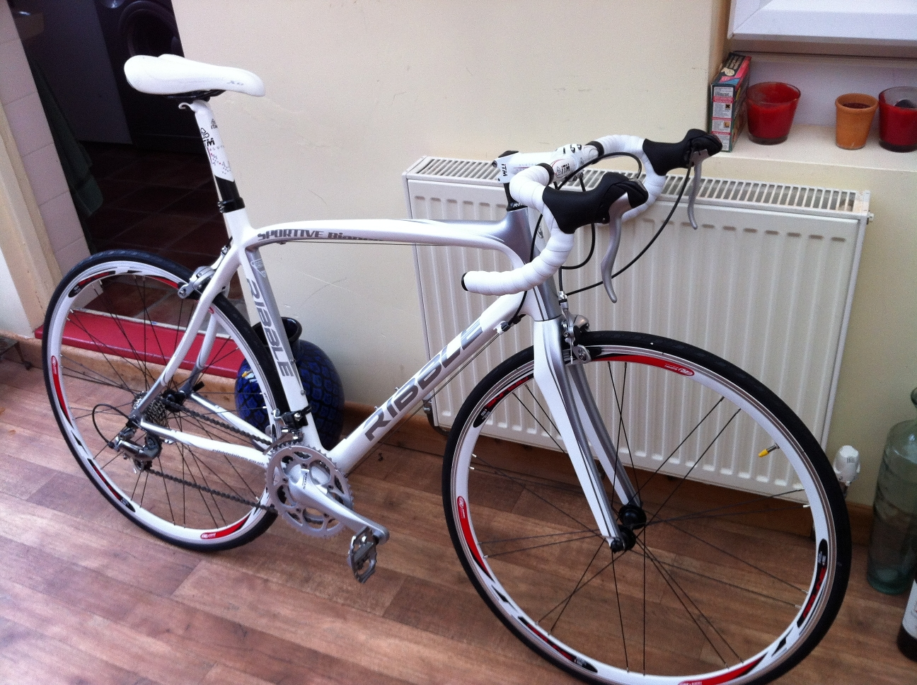 The bike is a white Ribble Sportive adult road racing bike, with a white saddle and white rims to the wheel.