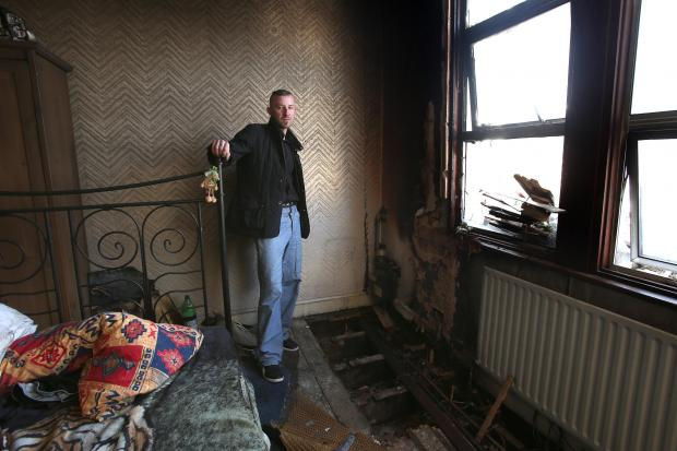 Reisdent Rafal Adam Duszyca inside the fire-damaged flat.