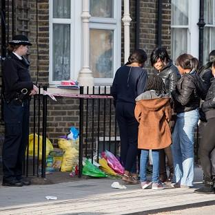 A police officer watches as a group of people gather at the scene in Hackney where Shereka Fab-Ann Marsh, 15, died after a sh