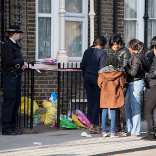 A police officer watches as a group of people gather at the scene in Hackney where Shereka Fab-Ann Marsh, 15, died after a shooting