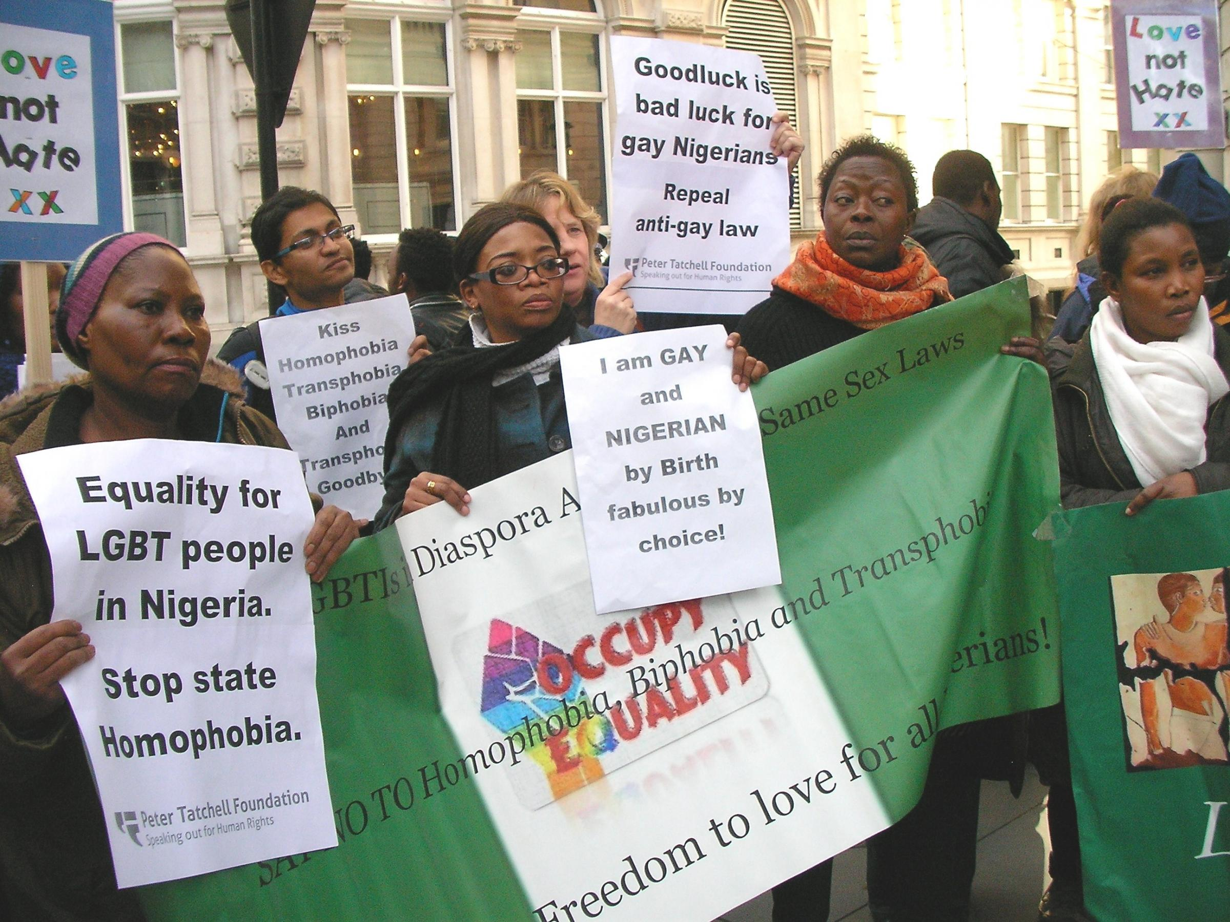 Flora Seggane, left, holding a Peter Tatchell placard during an LGBT rally in 2013