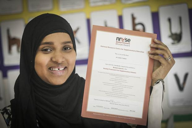 Ramla Farah, of A Class Tutors, holds the group's bronze award from the NRCSE