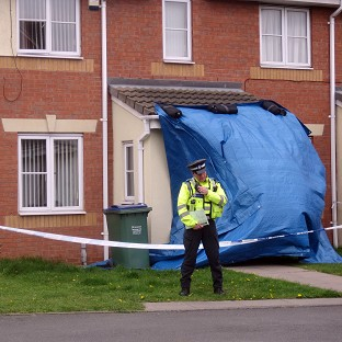 A police officer outside a property in Tividale, near Tipton where a 19-year-old woman was doused in hig