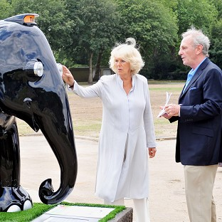 The Duchess of Cornwall is shown an elephant sculpture designed in the style of a London taxi by her brother Mark Shand
