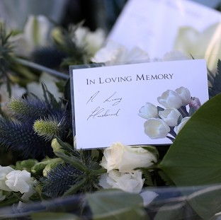Flowers left on behalf of Ann Maguire's husband Donald outside Corpus Christi Catholic College