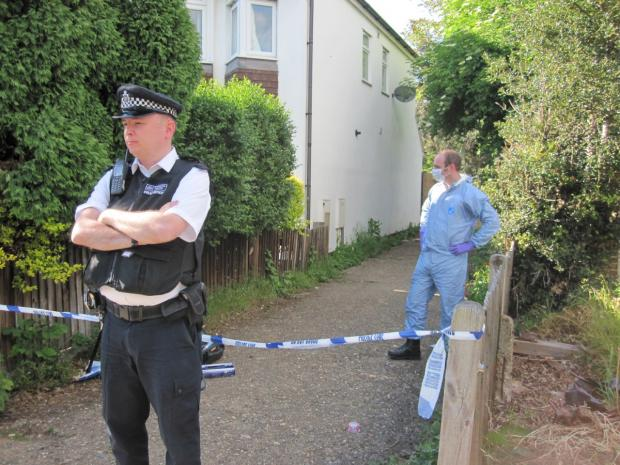 Police tape: Forensics officer at work as another stands guard
