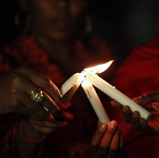 This Is Local London: People light candles during a vigil in Abuja to mark one month after the Nigerian schoolgirls were kidnapped (AP)