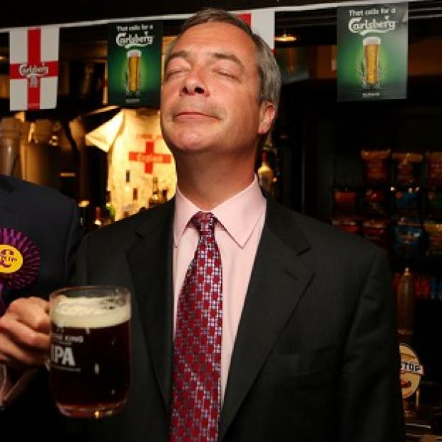 This Is Local London: Ukip leader Nigel Farage enjoys a pint in the Hoy and Helmet pub in South Benfleet, Essex, as his party makes election gains