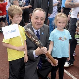 This Is Local London: Scotland's First Minister Alex Salmond with Craig Burns (aged seven) and Marilee Burns (aged five) and the Glasgow 2014 Queen's Baton at Meadowbank Stadium in Edinburgh. (Ben Birchall for Glasgow 2014)