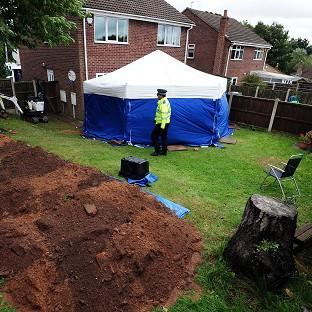 Police in the garden of a house in Mansfield, where the remains of William and Patricia Wycherley were discov