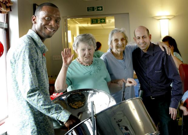 This Is Local London: Abdul Williams plays the steel pan drums for Brenda Beard, Margaret Farrell and activities coordinator David Fenton