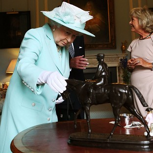 The Queen inspects a piece by French sculptor Pierre-Jules Mene during the filming of Antiques Roadshow in Belfast