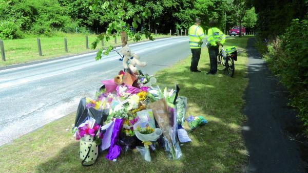 Floral tributes and teddy bears left by the side of the road in memory of a mother and son