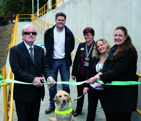 Geoff Jelly, of the Disability Alliance Network (Mid Surrey), cutting the ribbon to formally open the ramps