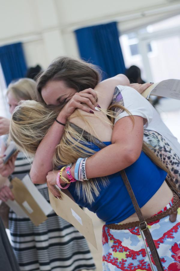 Two girls embrace after making the grade last year