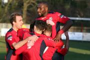 Winner: Hampton & Richmond Borough players mob striker Charlie Moone after his goal on Saturday