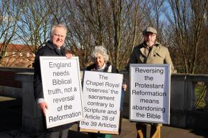 Protestant demonstrators explain Hampton Court Palace Catholic service protest