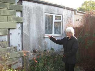 Kay Sims, aged 63, points to her decaying wall.
