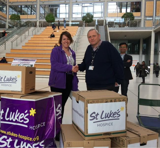 Rachel Wagstaff, director of fundraising, retail and communications at St Luke's Hospice, hands over the douments to Brent Council governance manager James Kinsella